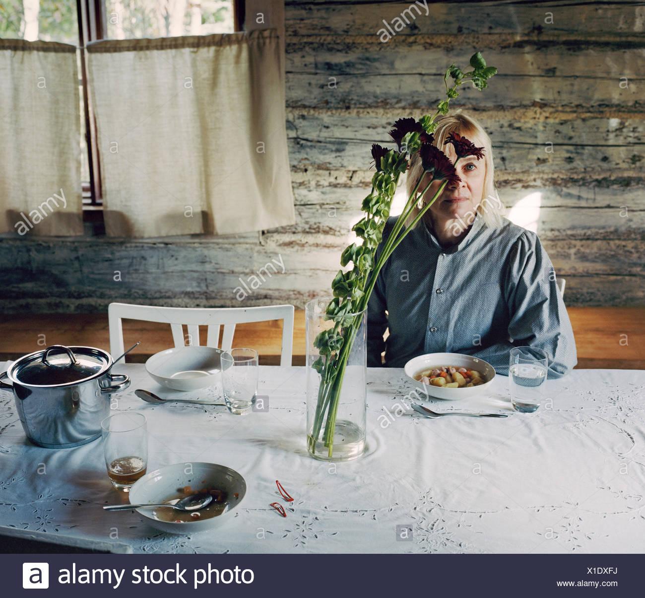 Finnland, Reife Frau, die am Tisch sitzen Stockbild