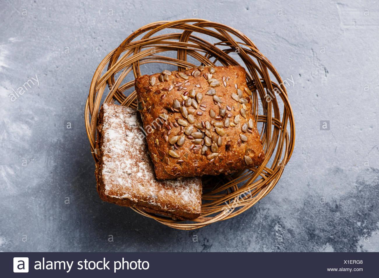 Frisches Getreide Brot Brötchen mit Sonnenblumenkernen in Weidenkorb auf grauem Beton Hintergrund Stockbild