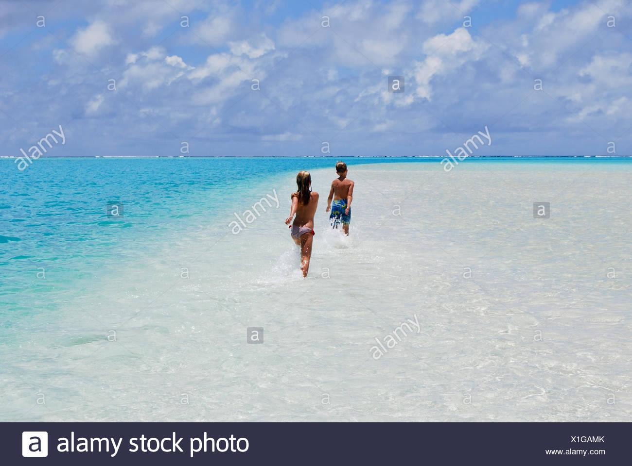 Zwei Kinder laufen auf Sandbank im Meer, Aitutaki, Cook-Inseln Stockbild