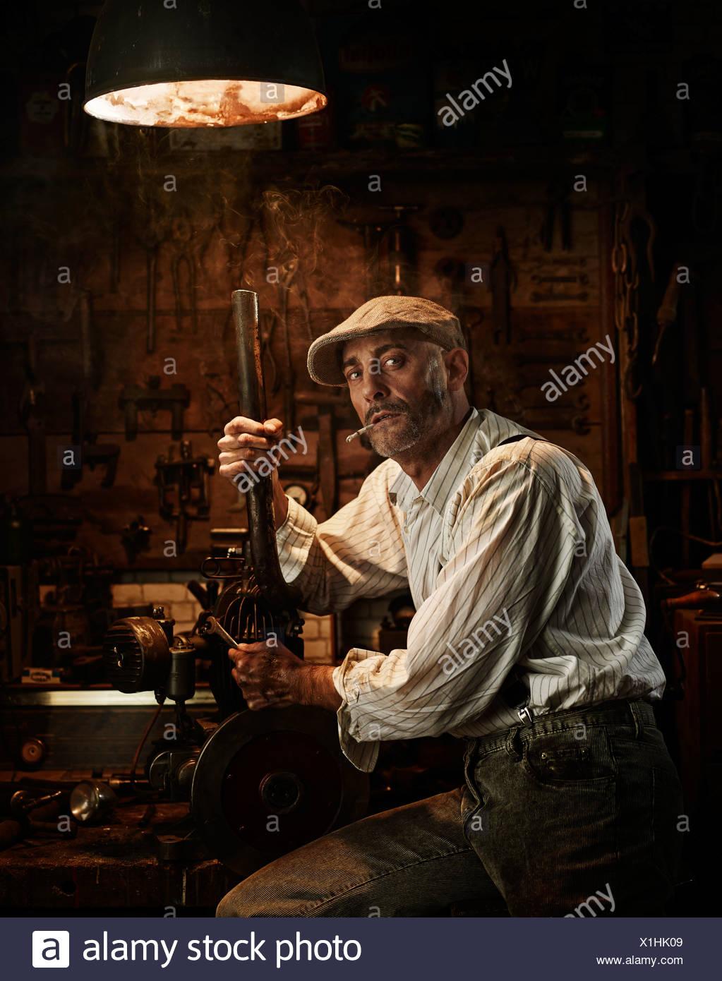 Mann mit Hut und Zigarette Reparatur eines Motors in einer Werkstatt Stockbild