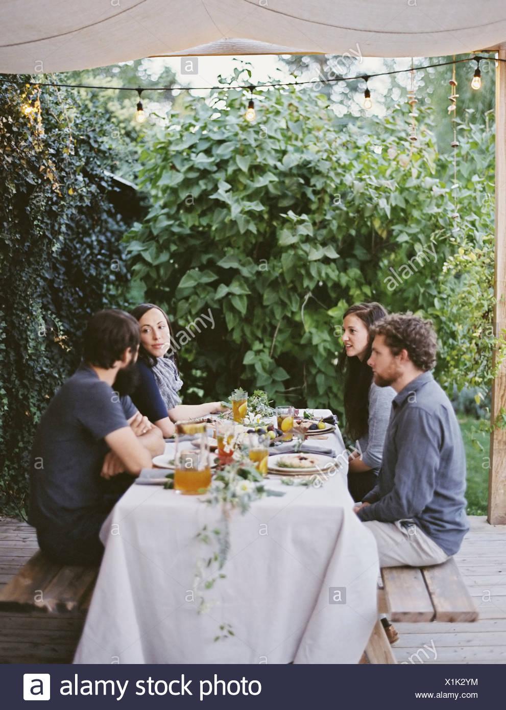 Vier Personen sitzen an einem Tisch im Garten Gedecke und Dekorationen auf ein weißes Tischtuch zwei Männer und zwei Frauen Stockbild