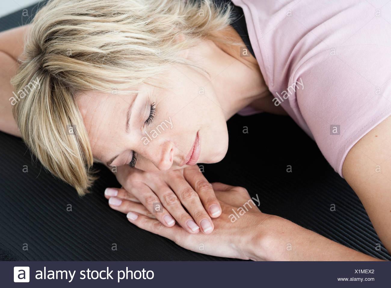 Entspannen Sie sich auf Yoga-Matte Frau Stockbild
