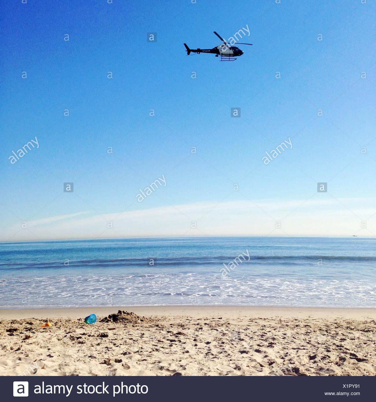 Hubschrauber fliegen über Strand Stockbild