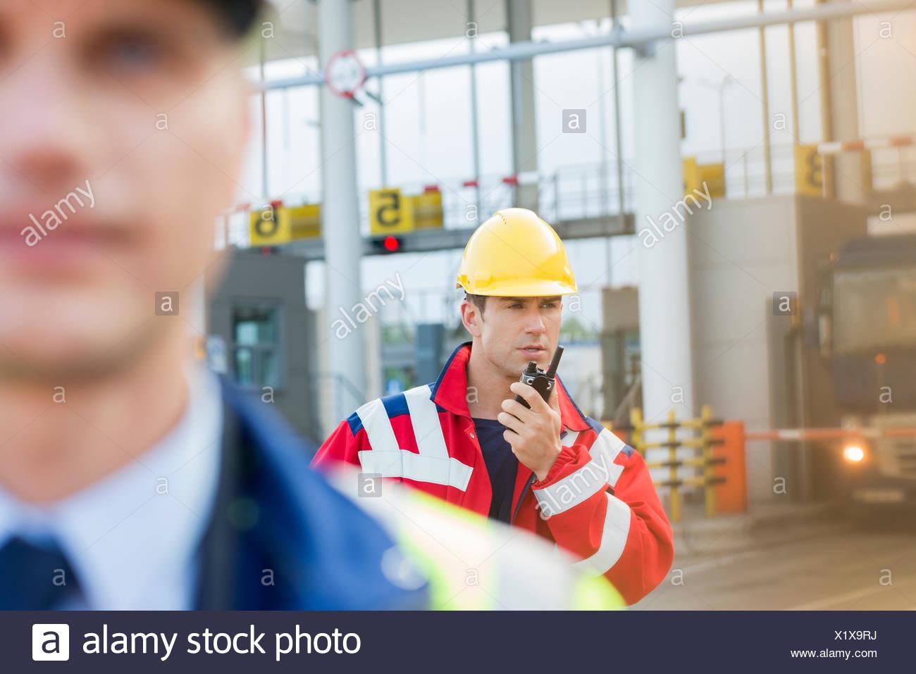 Männliche Arbeiter mit Walkie-talkie mit Kollegen im Vordergrund auf Werft Stockbild