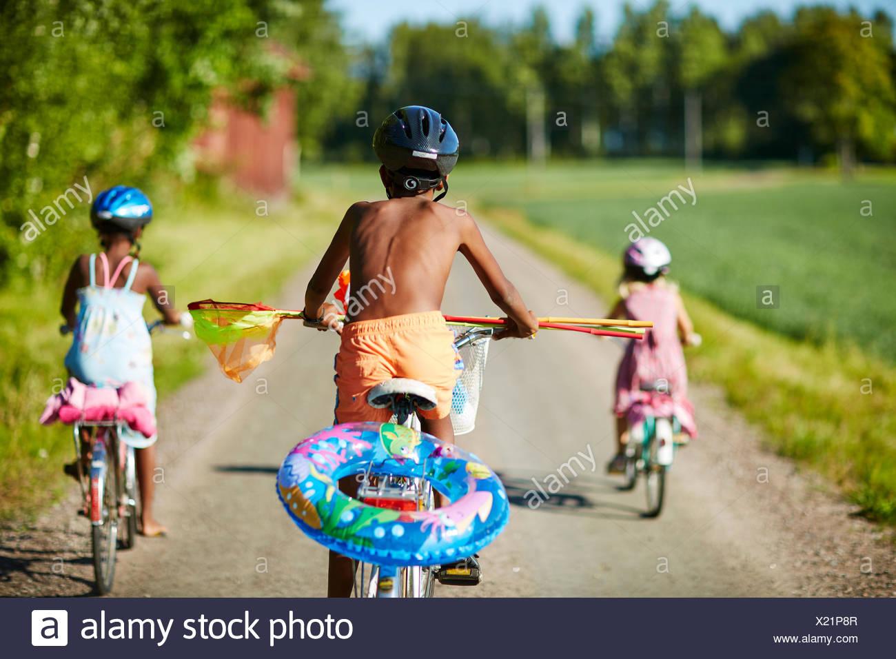 Kinder Radfahren auf einer Landstraße in Gullspang, Schweden Stockbild