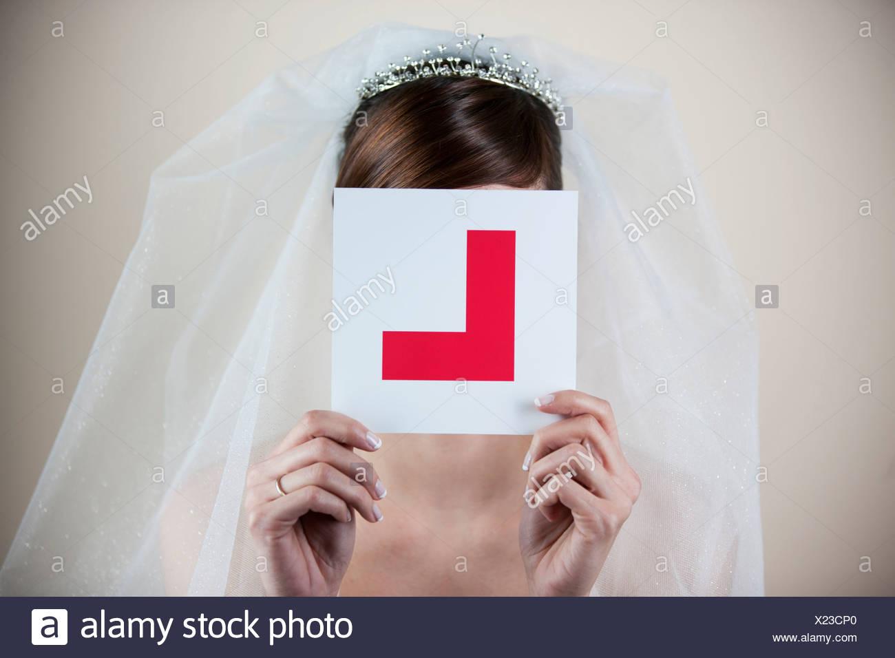 Eine junge Braut eine Learner Permit Halteplatte vor ihr Gesicht Stockbild