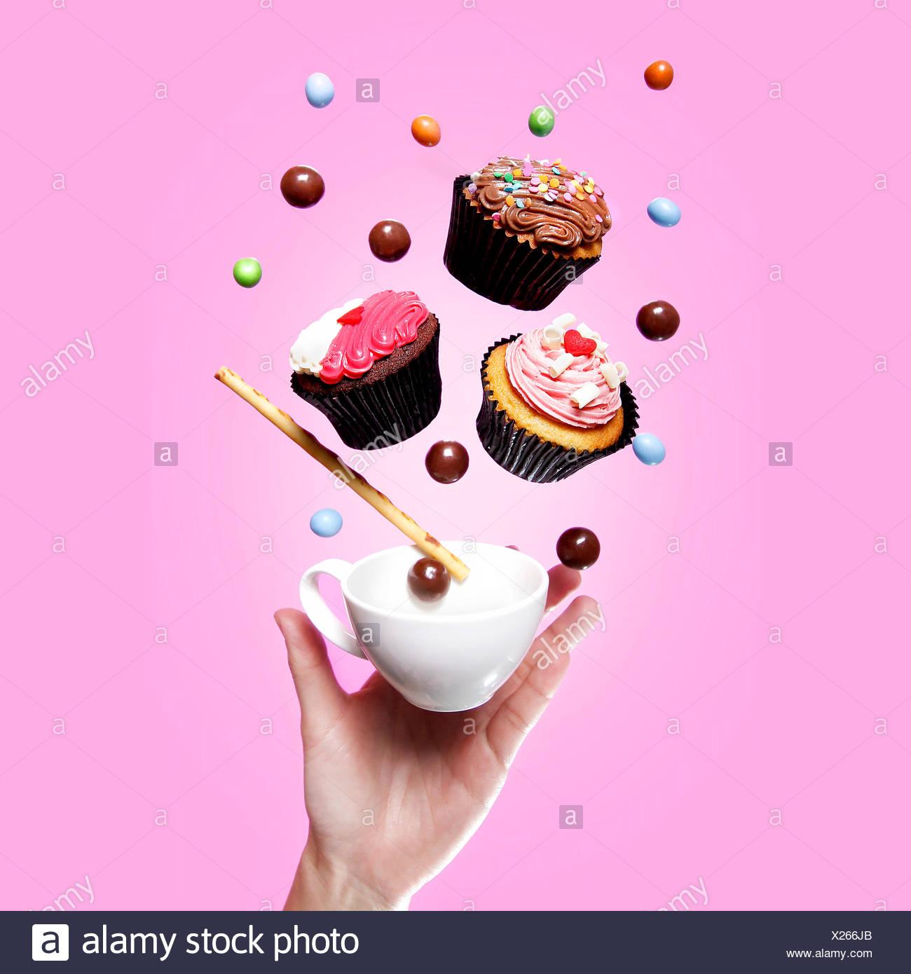 Fliegen, Cupcakes, Teetasse, Süßigkeiten und eine hand Stockbild