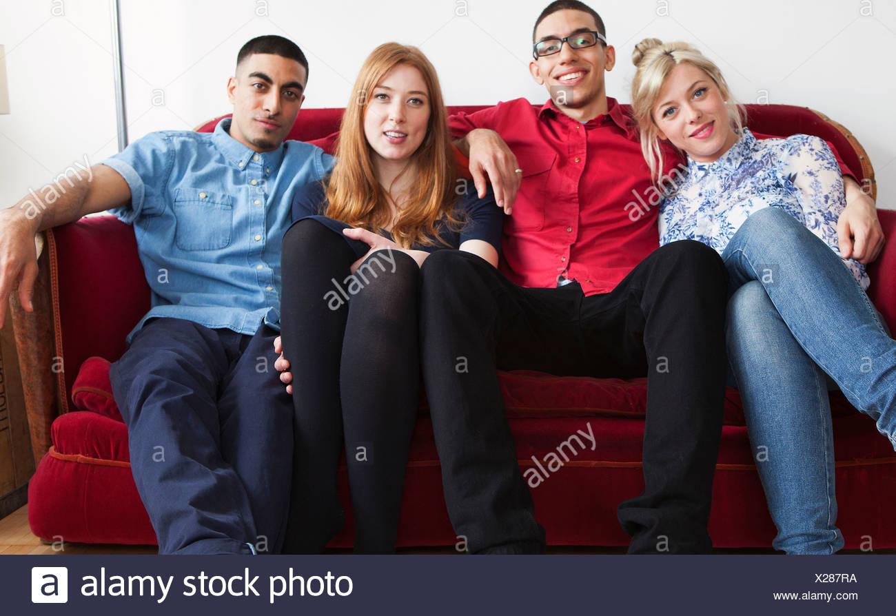 Vier junge Erwachsene auf sofa Stockbild