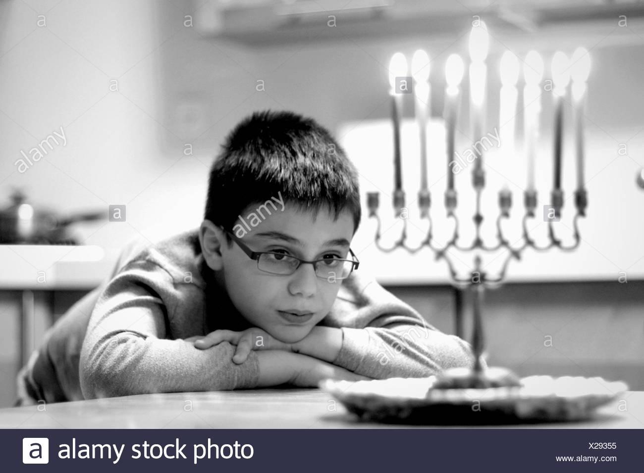 Süsser Boy Blick auf Kerzen beim Sitzen am Tisch zu Hause Stockbild