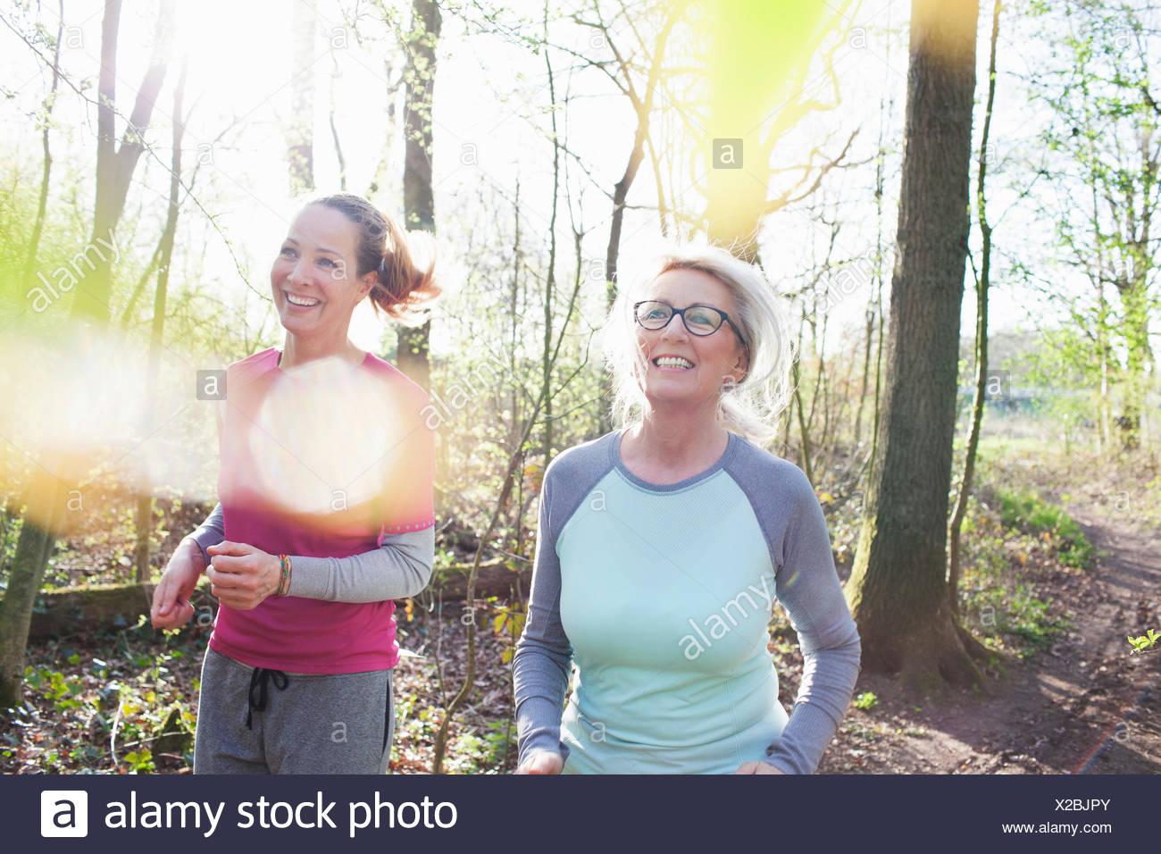 Frauen Joggen im Wald lächelnd Stockbild