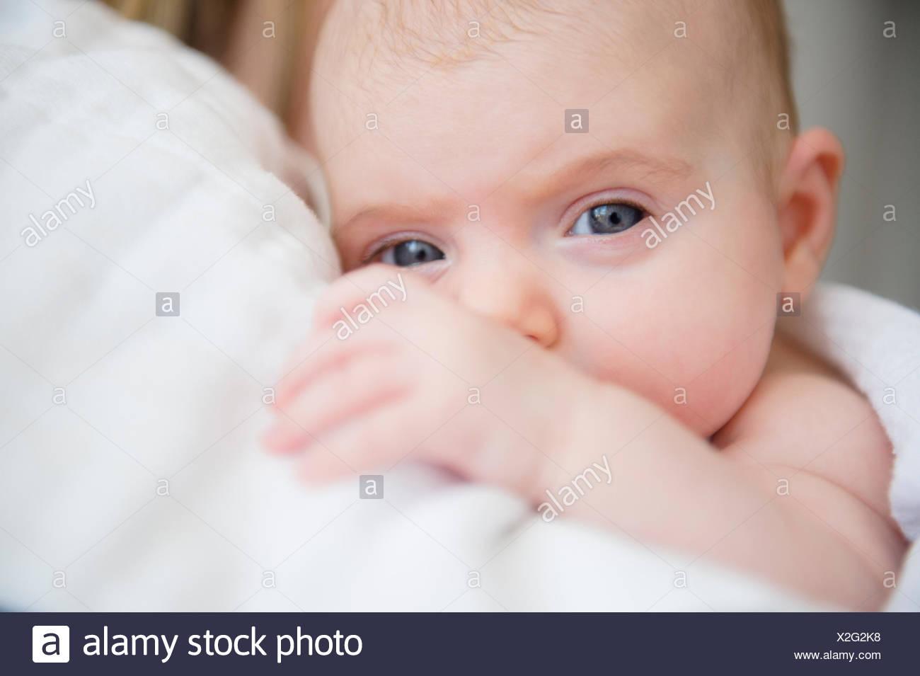 Porträt des Mädchens (2-5 Monate) im Arm der Mutter Stockbild