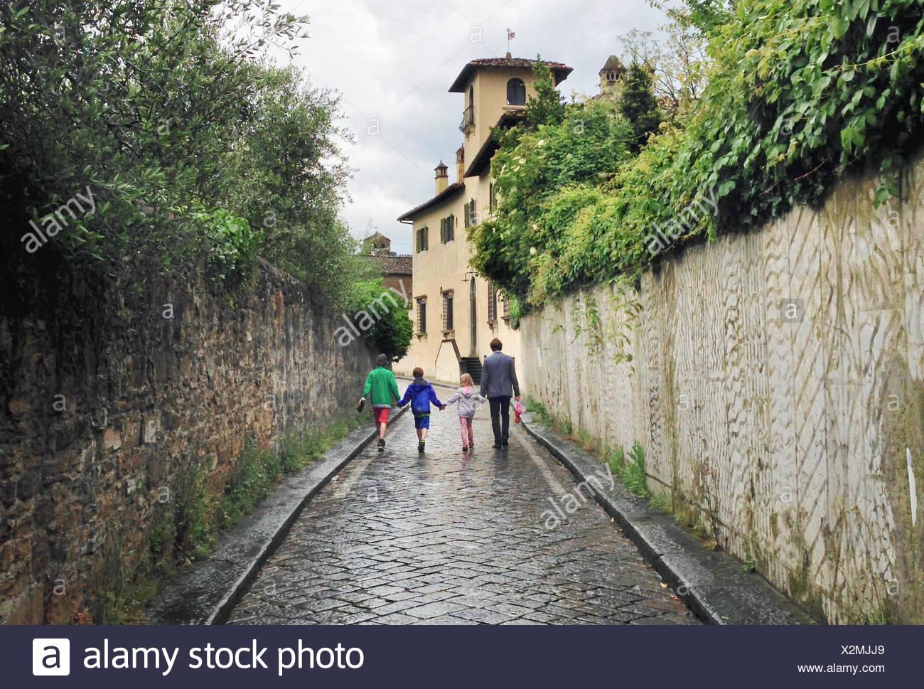 Italien, Toskana, Florenz, Vater mit drei Kindern (10-11, 12-13) walking an regnerischen Tag Stockbild