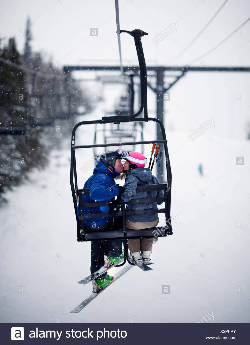 Ein paar Küssen auf dem Sessellift in weich fallenden Schnee. Stockbild