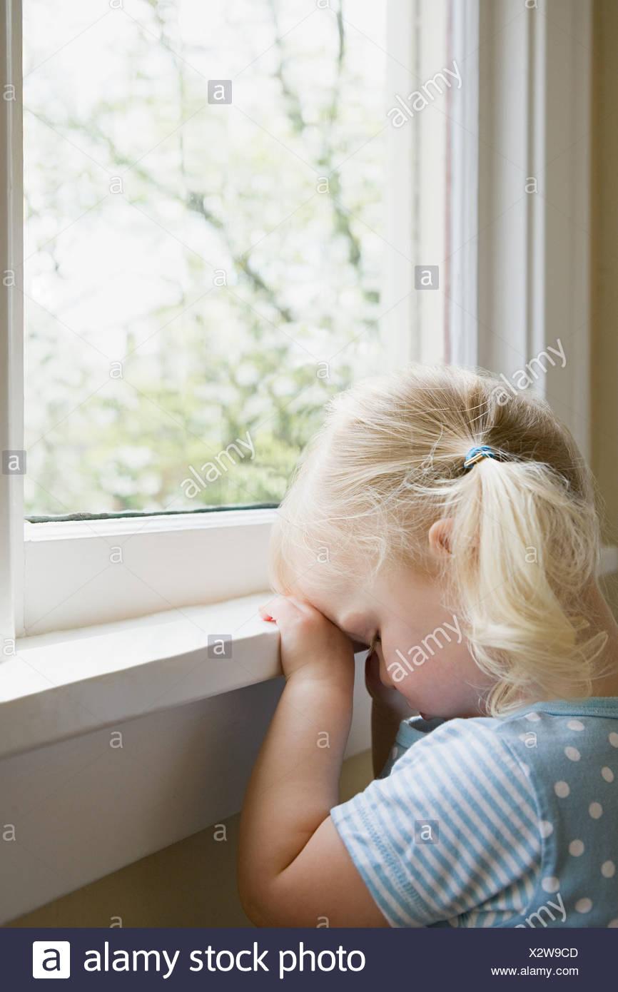 Trauriges Mädchen durch Fenster Stockbild