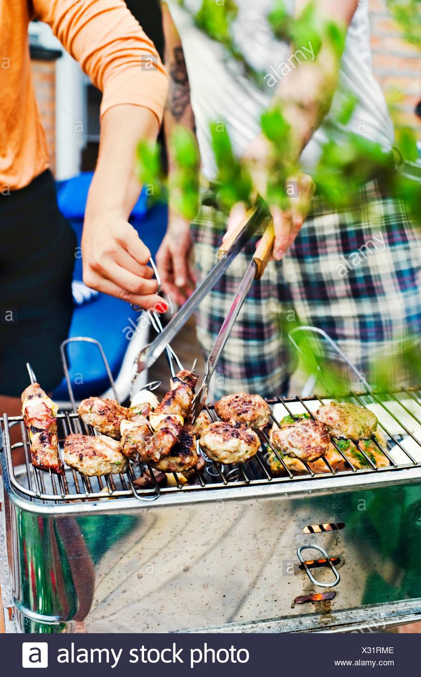 Schweden, Uppland, Danderyd, paar grillen Fleisch am Grill Stockbild