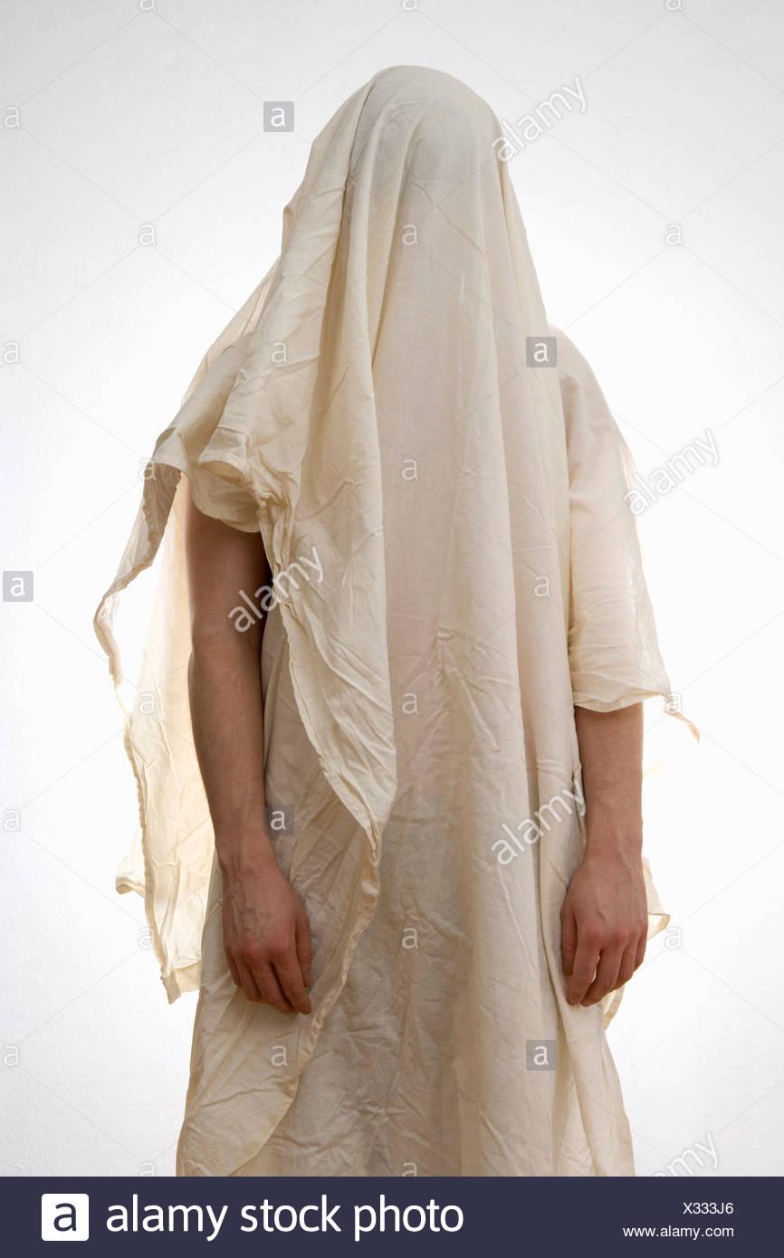 Eine Person, die unter ein weißes Blatt Stockbild