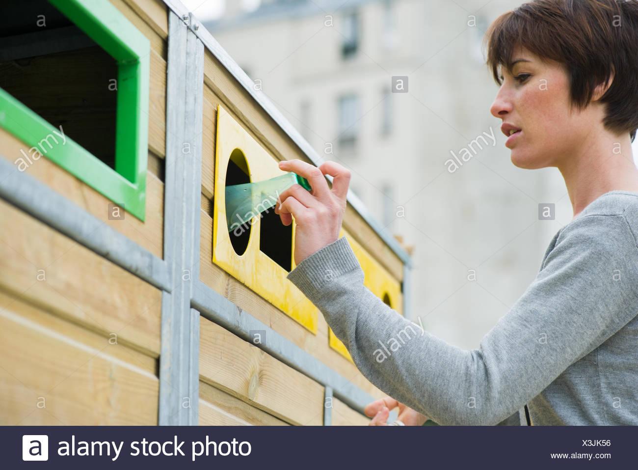 Frau Plastikflasche in Recyclingbehälter platzieren Stockbild