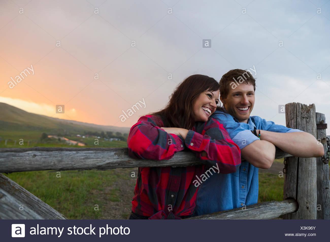 Paar stützte sich auf ländliche Zaunpfahl bei Sonnenuntergang Stockbild