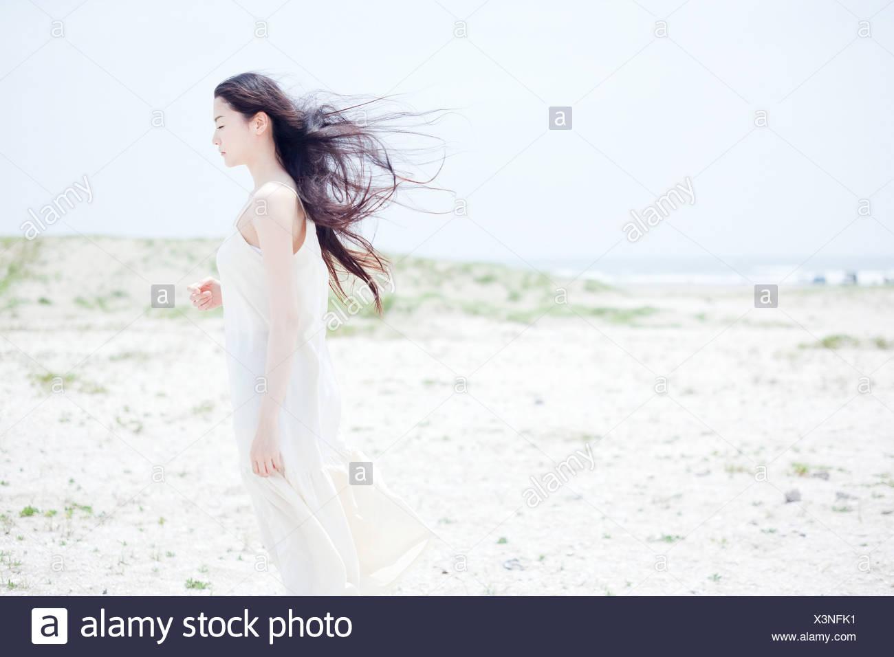 Junge Frau mit langen windigen schwarze Haare am Strand Stockbild