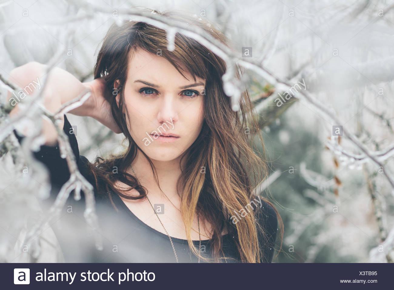 Porträt der jungen Frau, die unter den gefrorenen Zweige Stockbild