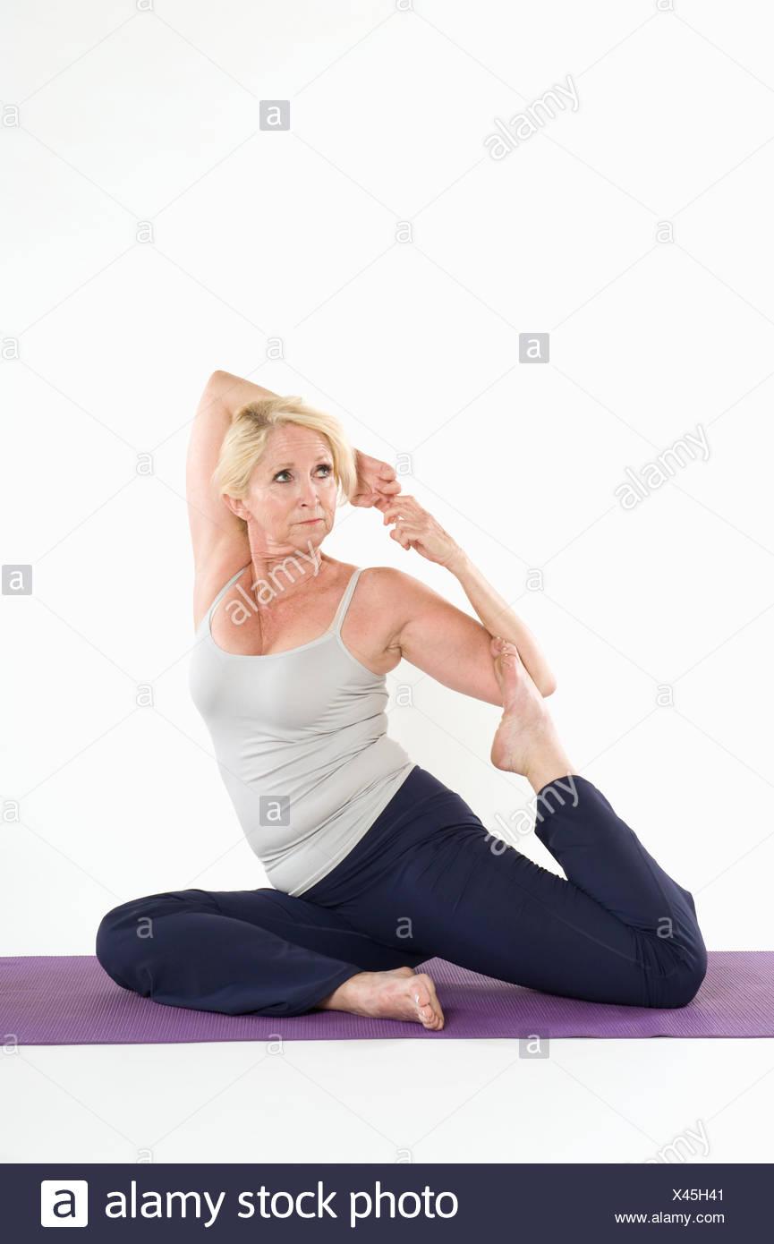 Mittlere gealterte Frau tun erstreckt sich auf Yoga-Matte über weißem Hintergrund Stockbild