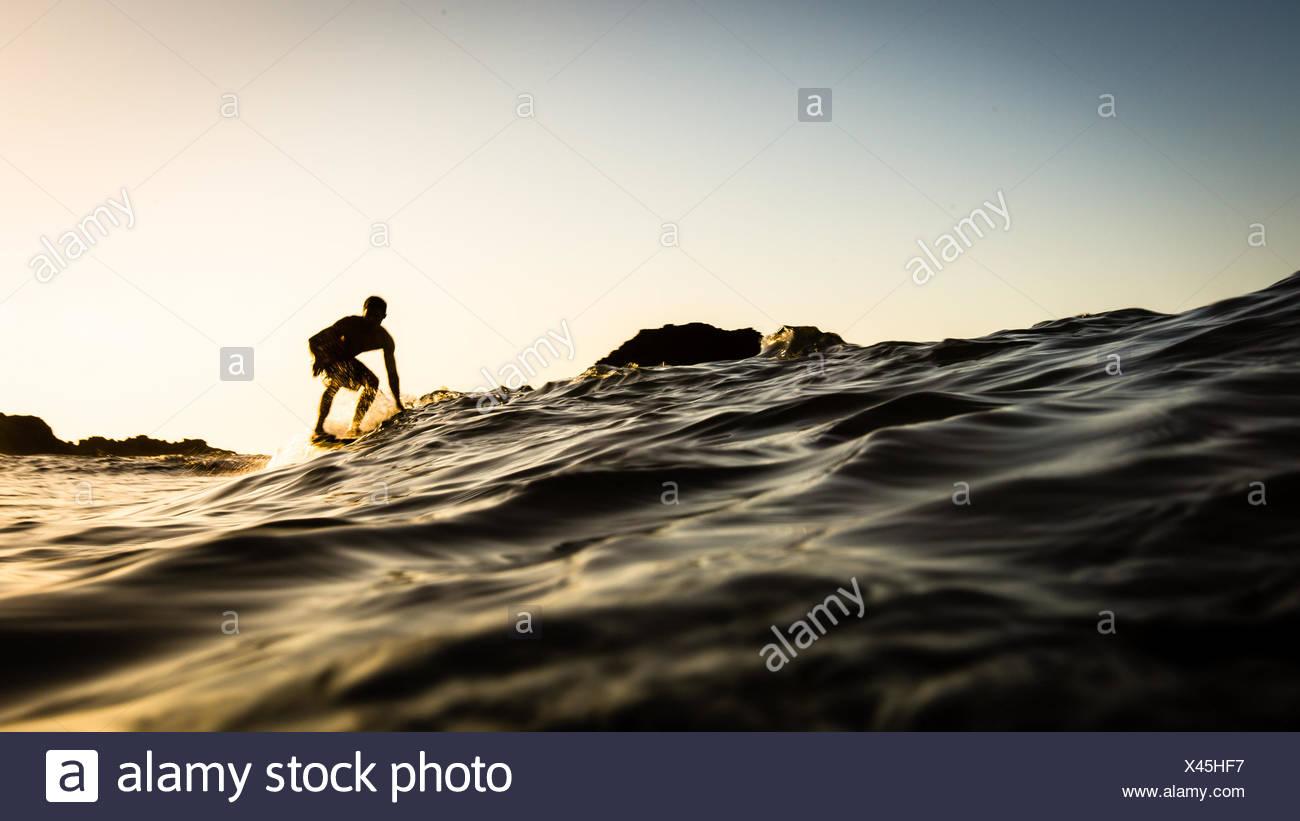 USA, California, Los Angeles County, Malibu, Surfer bei Sonnenuntergang Stockbild