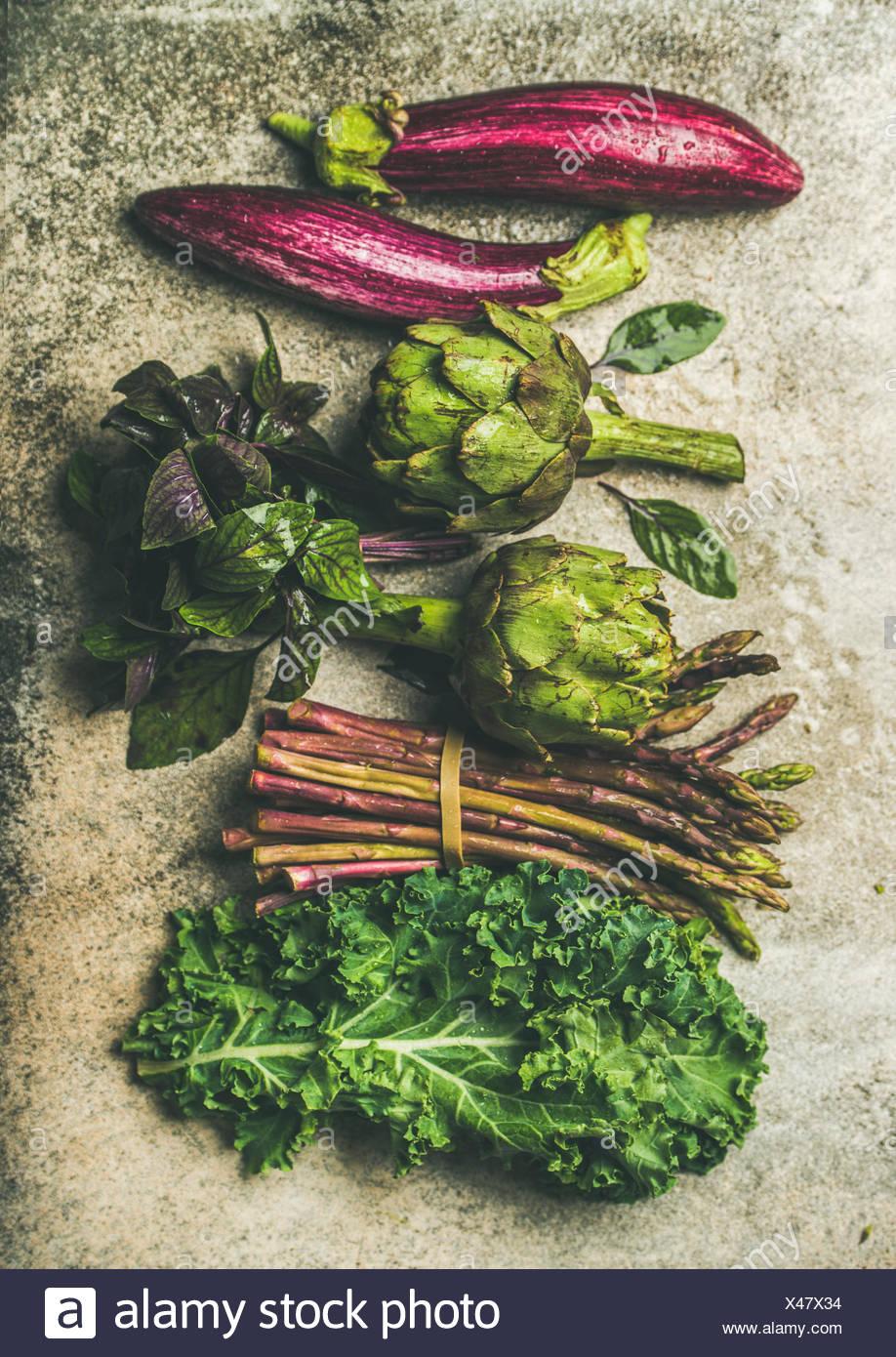 Flachbild-lay von Grün und Violett frisches Gemüse Vielfalt über konkreten Hintergrund, Ansicht von oben. lokalen, saisonalen Produkten für gesundes Kochen. eggplans, Bohnen, Stockbild