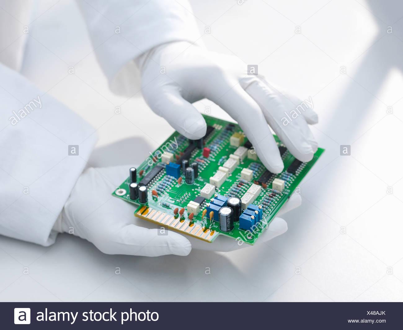 Hände halten Platine Stockbild