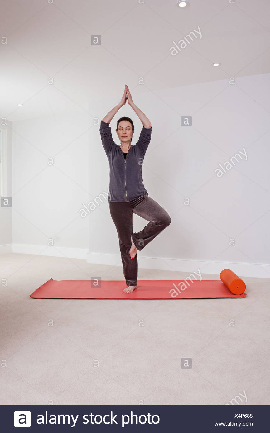 Frau praktizieren Yoga auf der Matte Stockbild