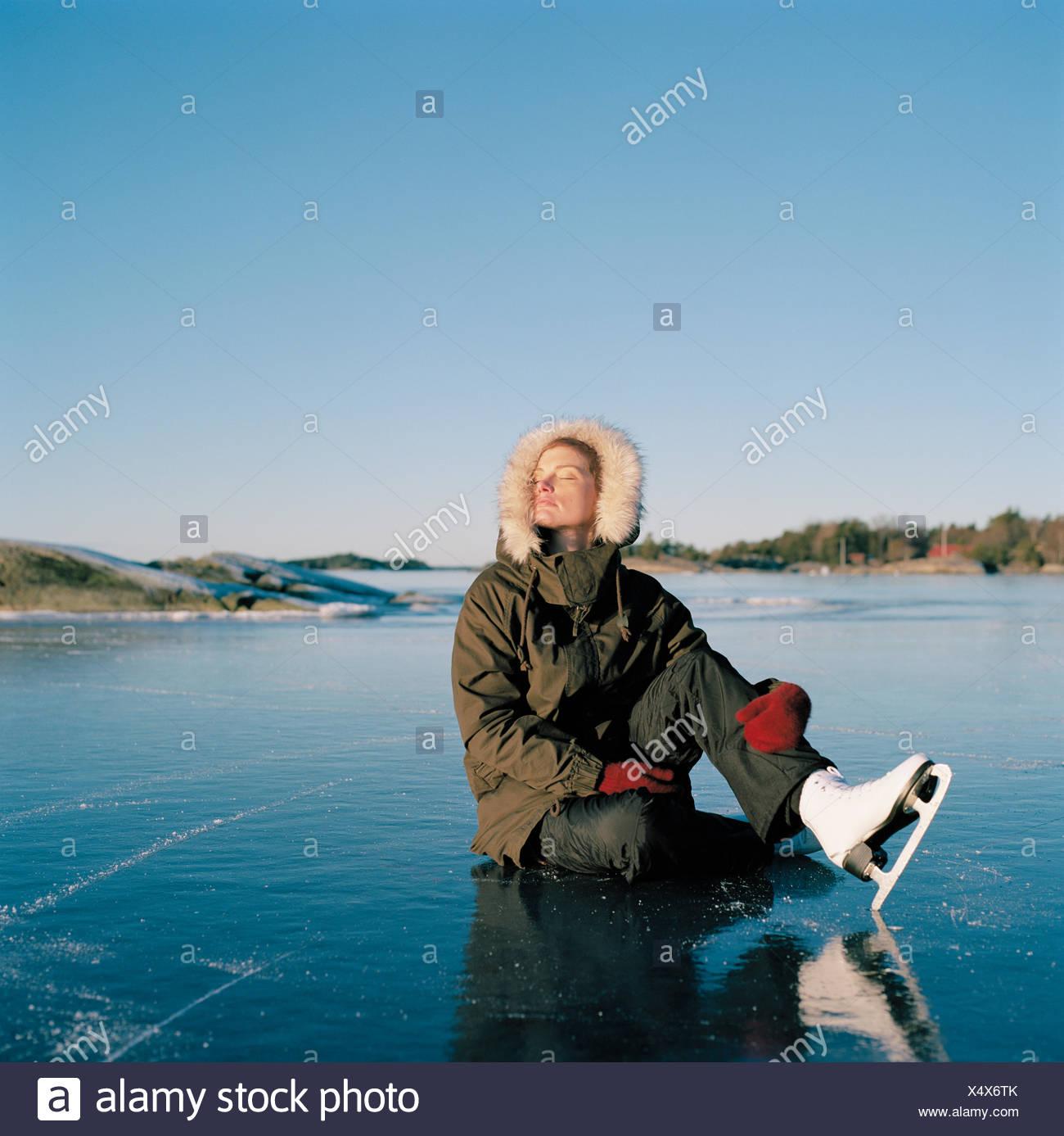 Schweden, Uppland, Varmdo, Bjorno, Mitte Erwachsene Frau sitzt auf dem zugefrorenen See Stockbild