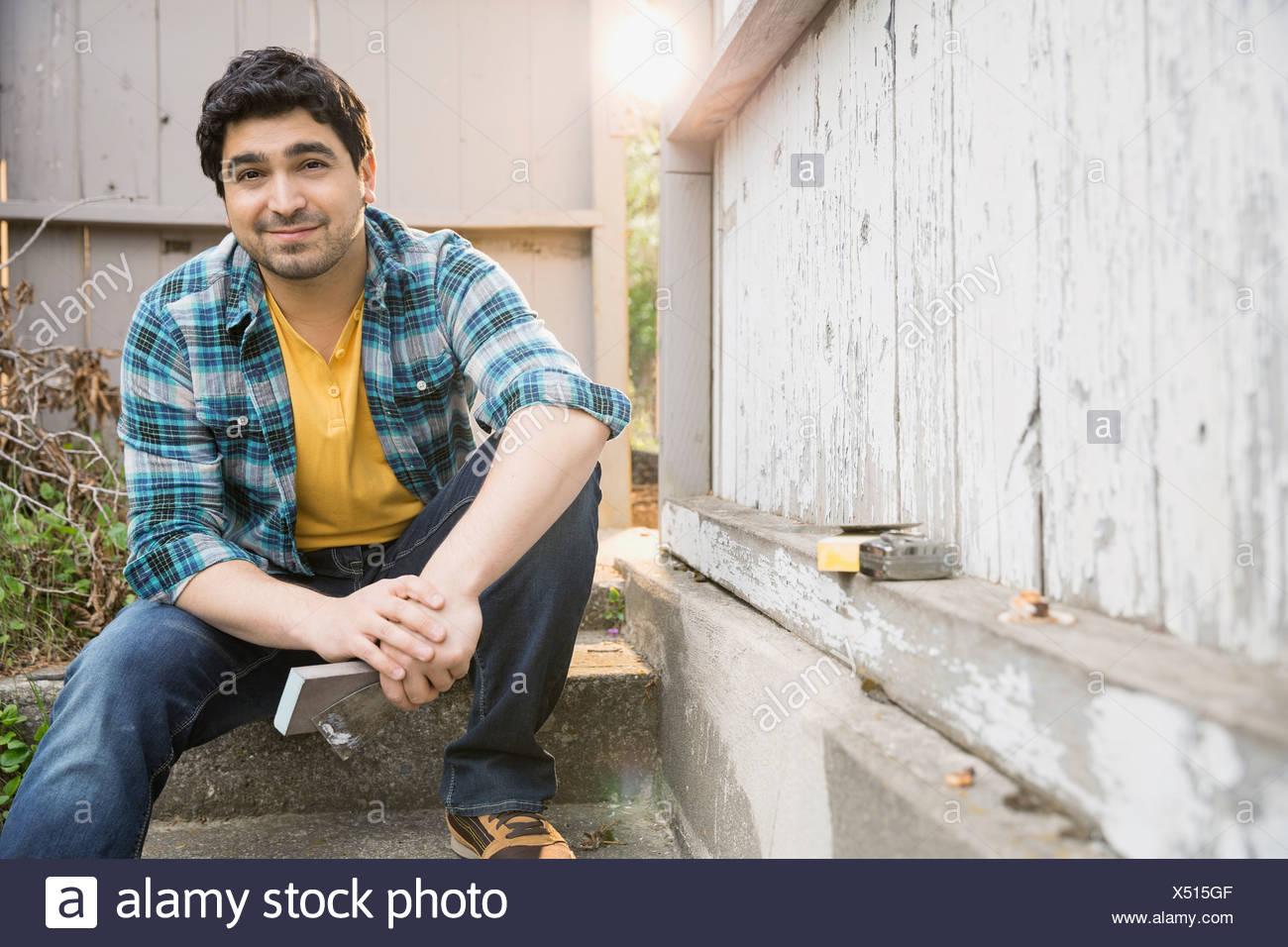 Porträt von lächelnden Mann mit Werkzeugen am Zaun Stockbild