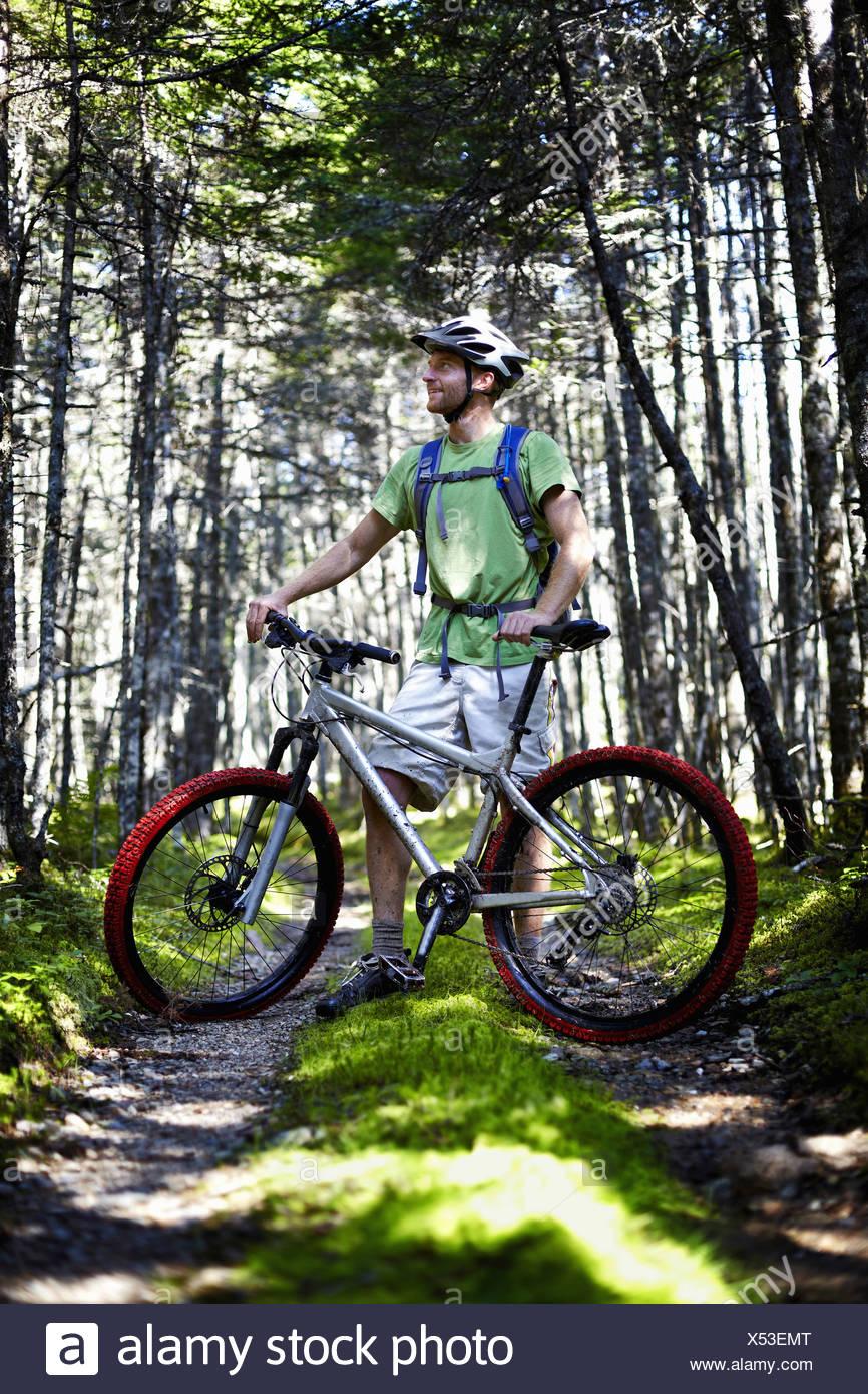 Ein Mountainbiker in einen Helm mit einem Rucksack tatenlos sein Fahrrad im Wald Stockbild