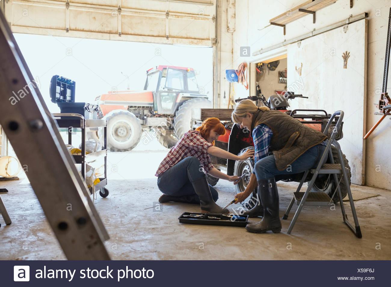 Mutter und Tochter Quadbike Rad reparieren Stockbild