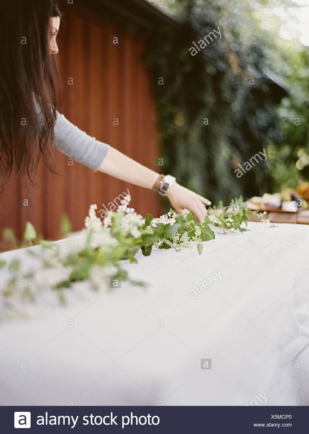 Eine Frau mit langen Haaren vom Tisch gelegt außerhalb mit einem weißen Tuch und zentrale Laub Tisch Dekoration Maßgedecke Stockbild