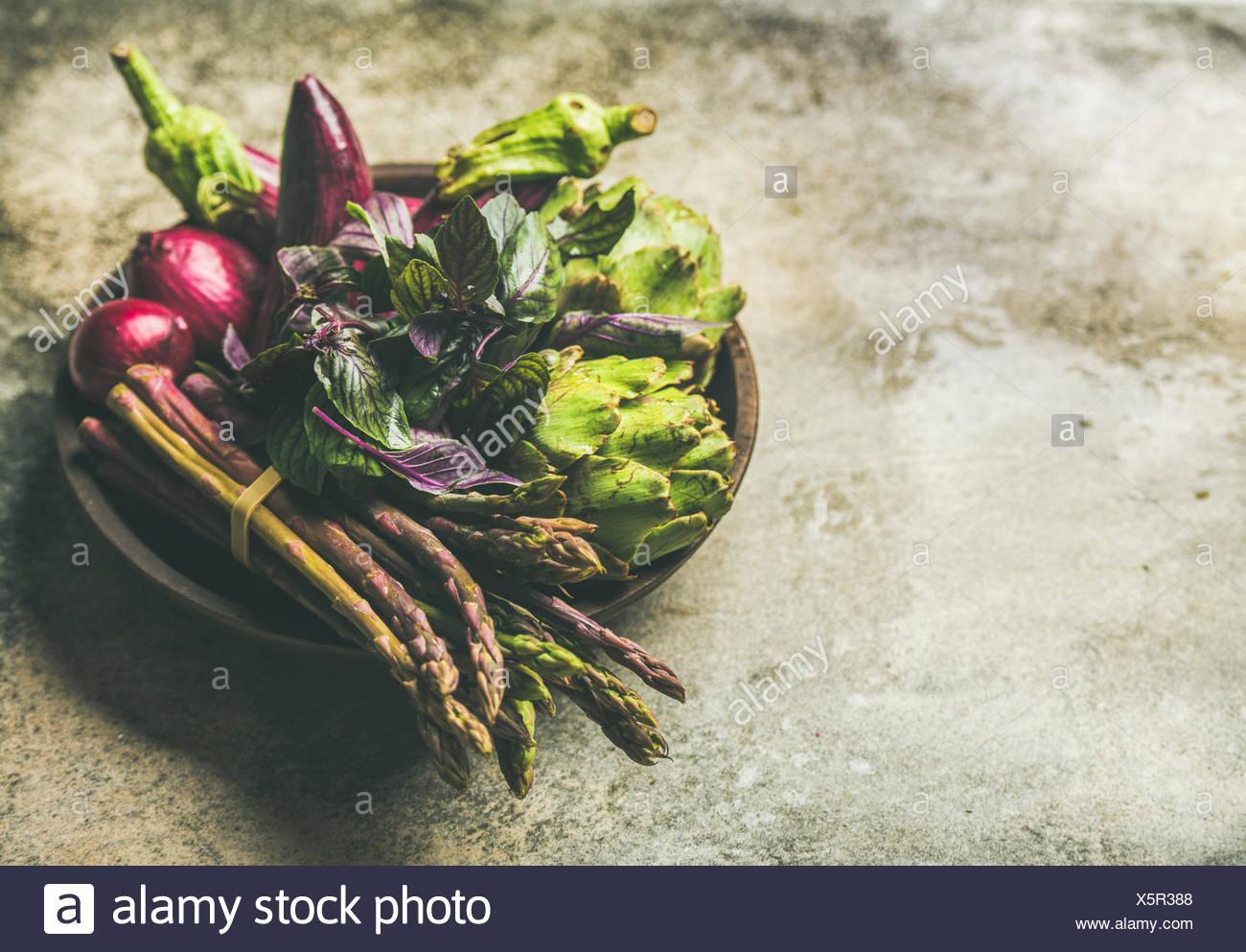 Grün und lila Gemüse auf die Platte über der konkreten Hintergrund, selektiver Fokus, kopieren. lokale Produkte für gesundes Kochen. eggplans, Bohnen, Kohl, Stockbild