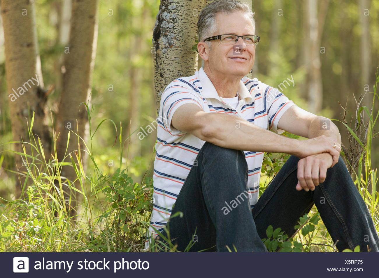 Mann mittleren Alters Tagträumen, wie er von Bäumen entspannt Stockbild