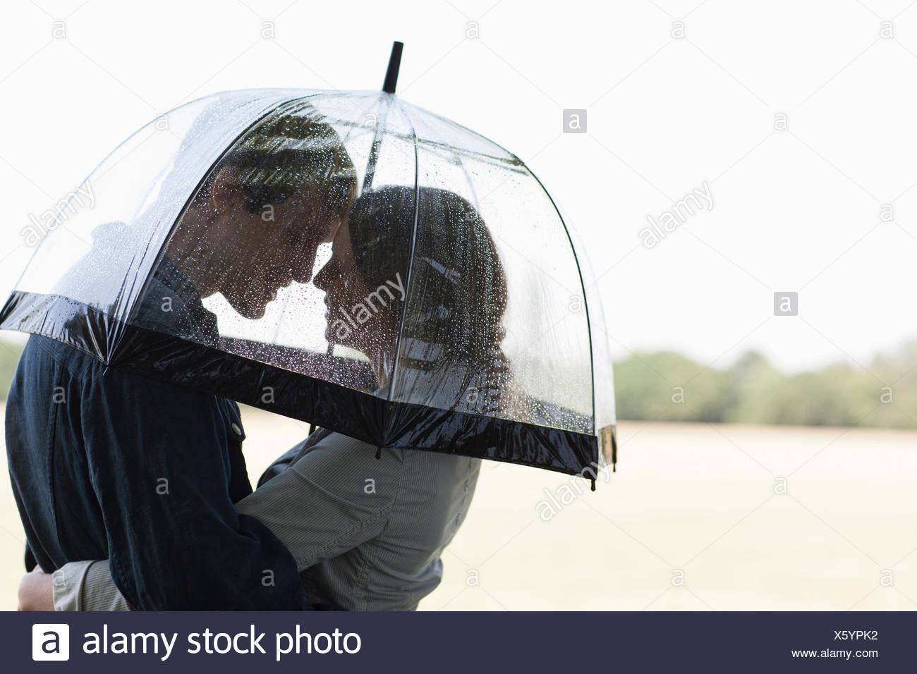 Paar im Regen unter Dach umarmt Stockbild
