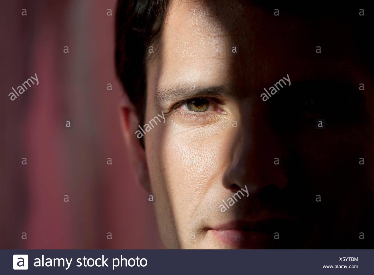 Close-up Portrait eines Mannes mit einem halben Gesicht versteckt in der Dunkelheit Stockbild