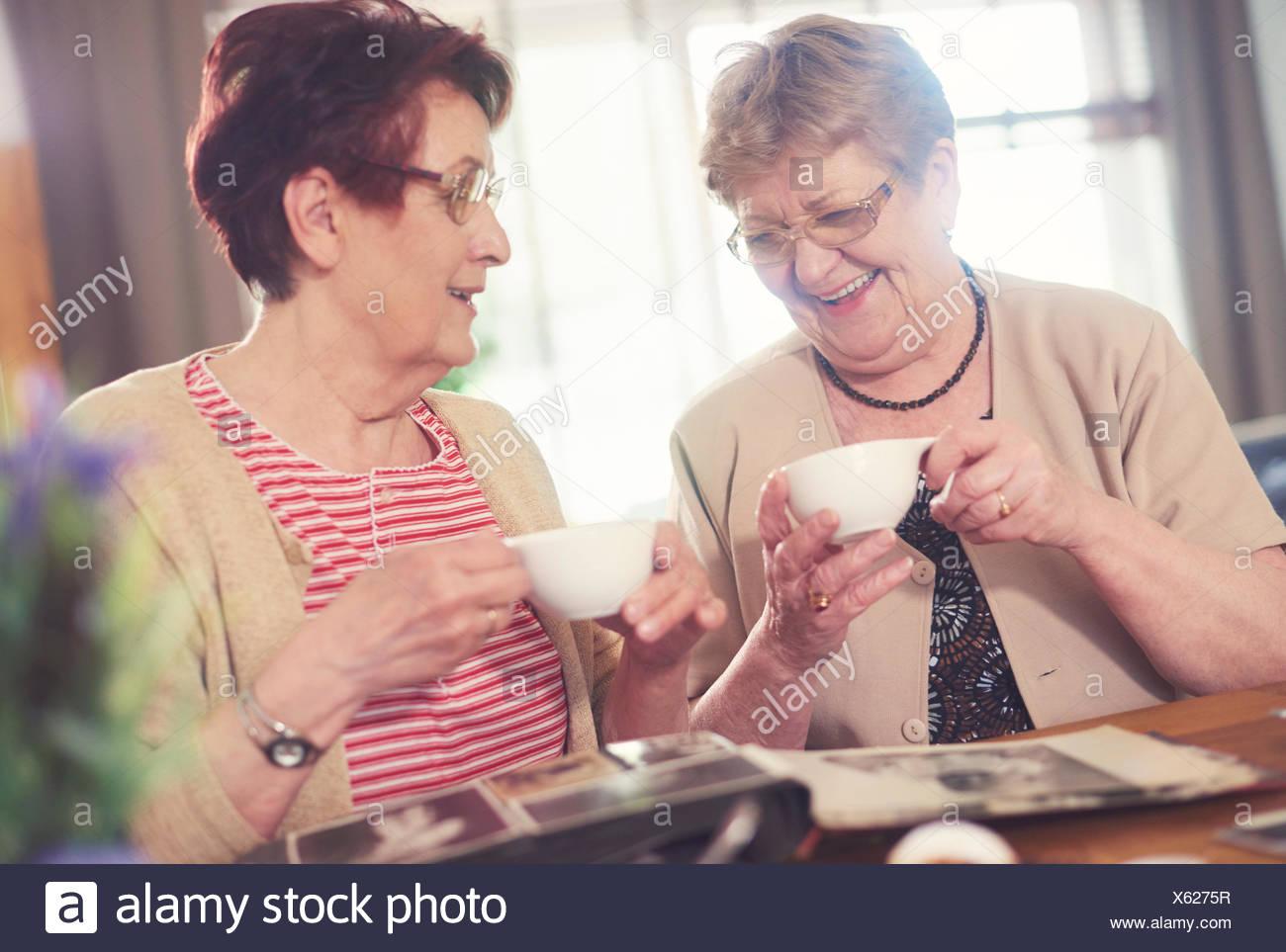 Zwei alte Frauen lachen beim betrachten Fotoalbum auf Tisch Stockbild