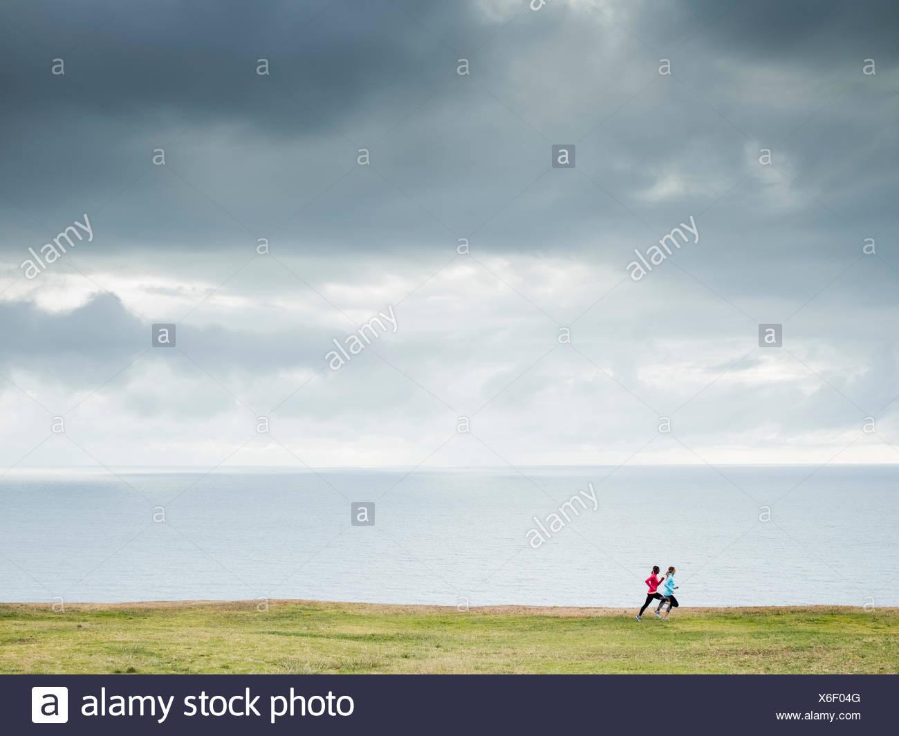 Zwei Frauen Joggen entlang der Küste-Läufer Stockbild
