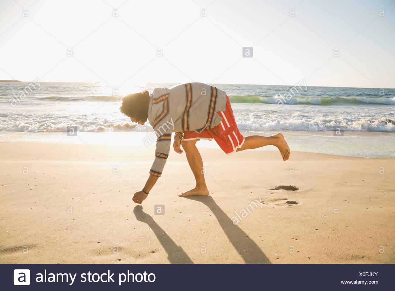 Mann, die Abholung Muscheln am Strand Stockbild