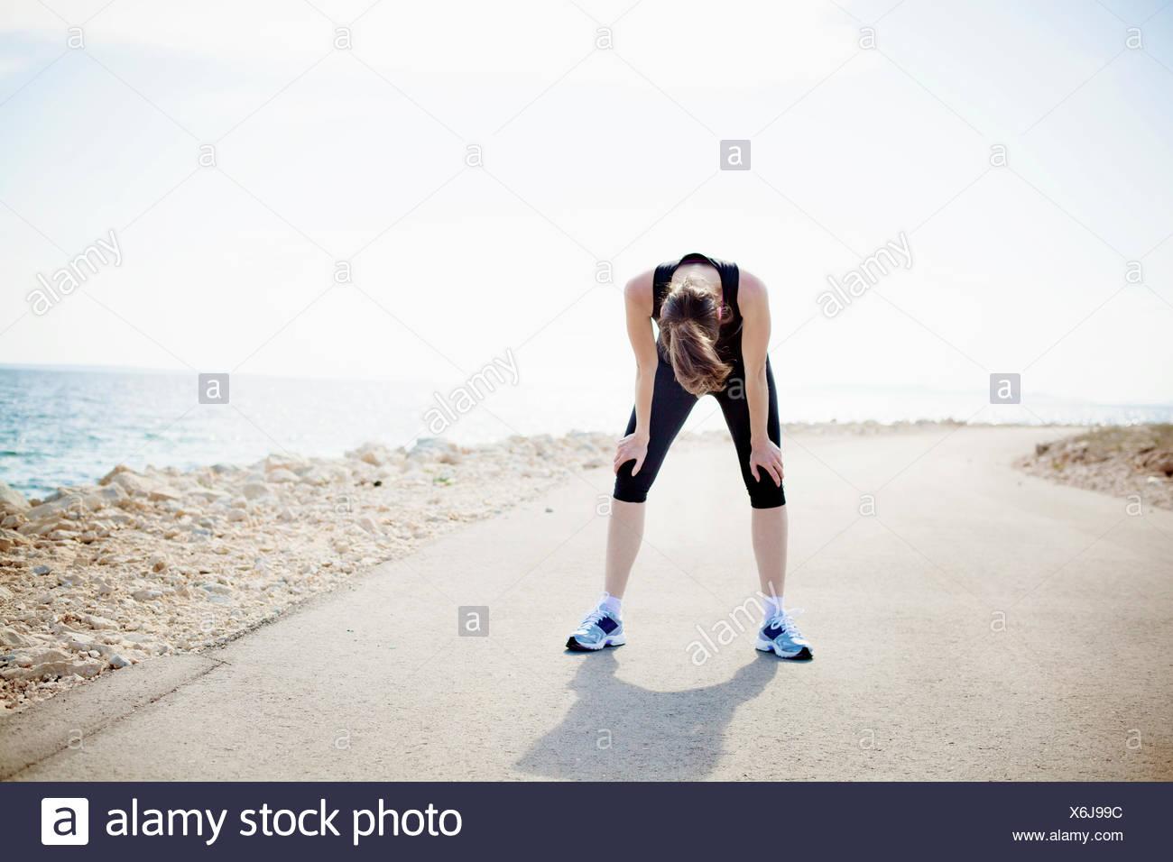 Frau in Sportkleidung auf Wasser Weg Stockbild