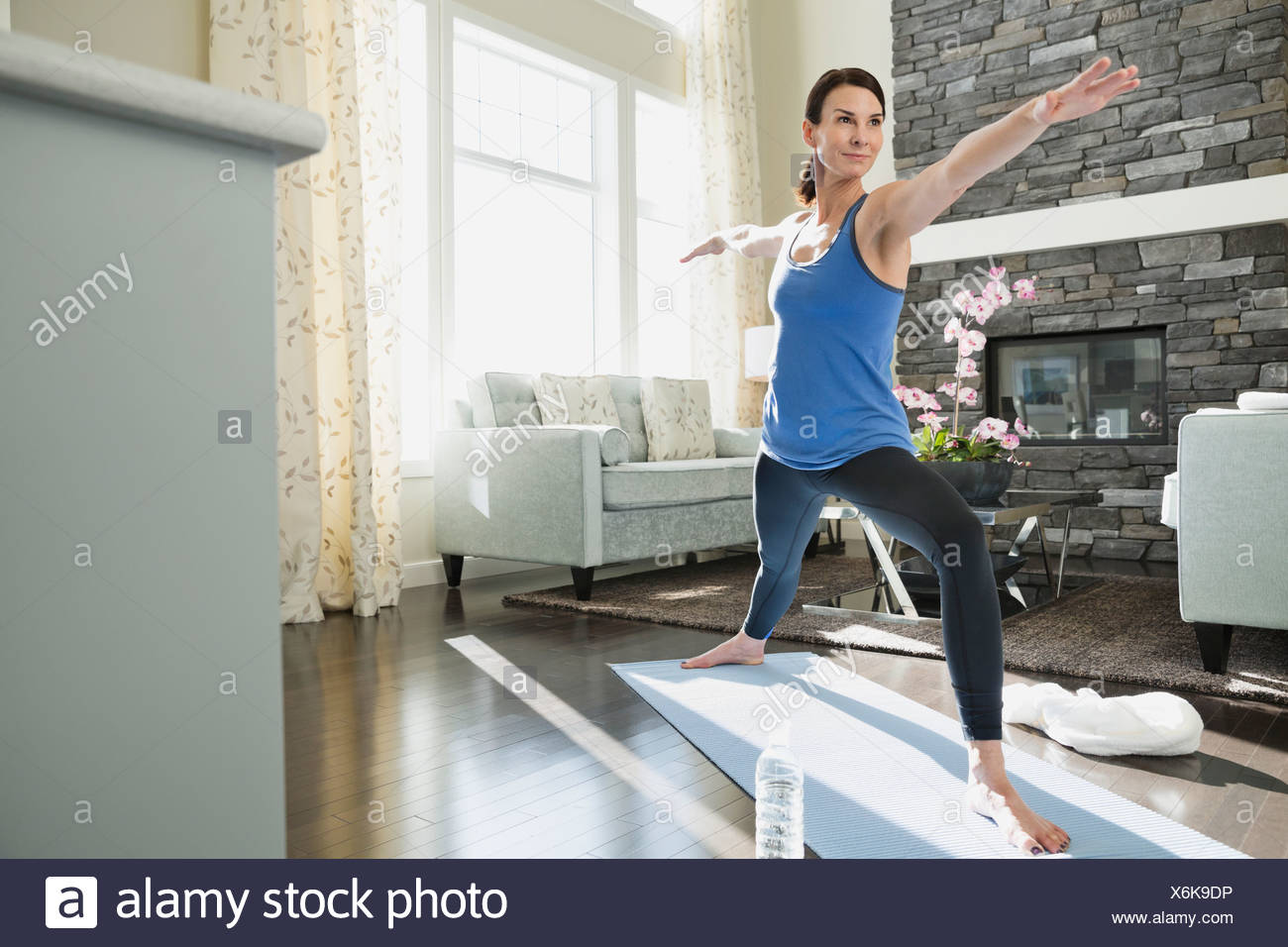 Reife Frau erstreckt sich auf Yoga-Matte Stockbild
