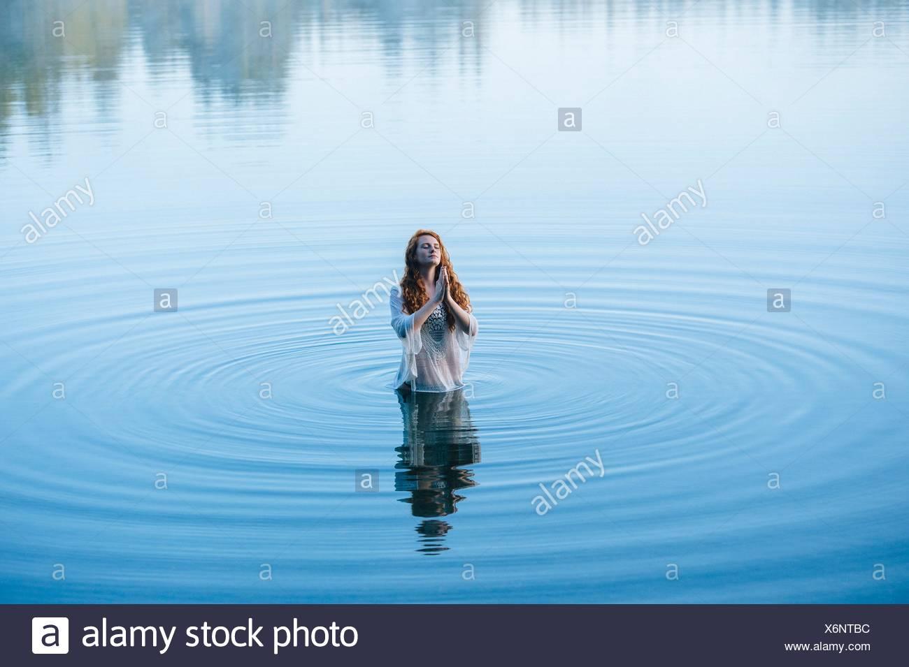 Junge Frau im See kräuselt sich mit geschlossenen Augen zu beten Stockbild