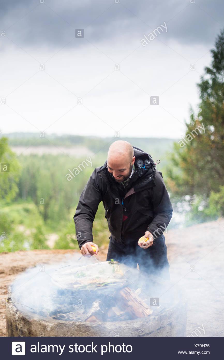 Ein Mann Kochen am Lagerfeuer Stockbild