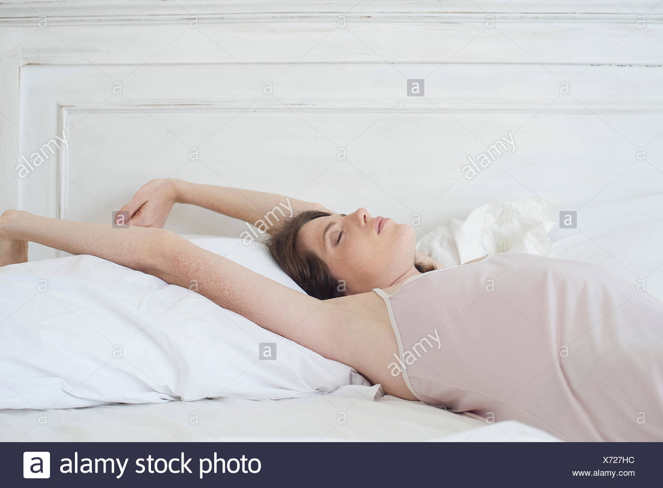 Frau liegt auf dem Rücken im Bett ausdehnen Stockbild