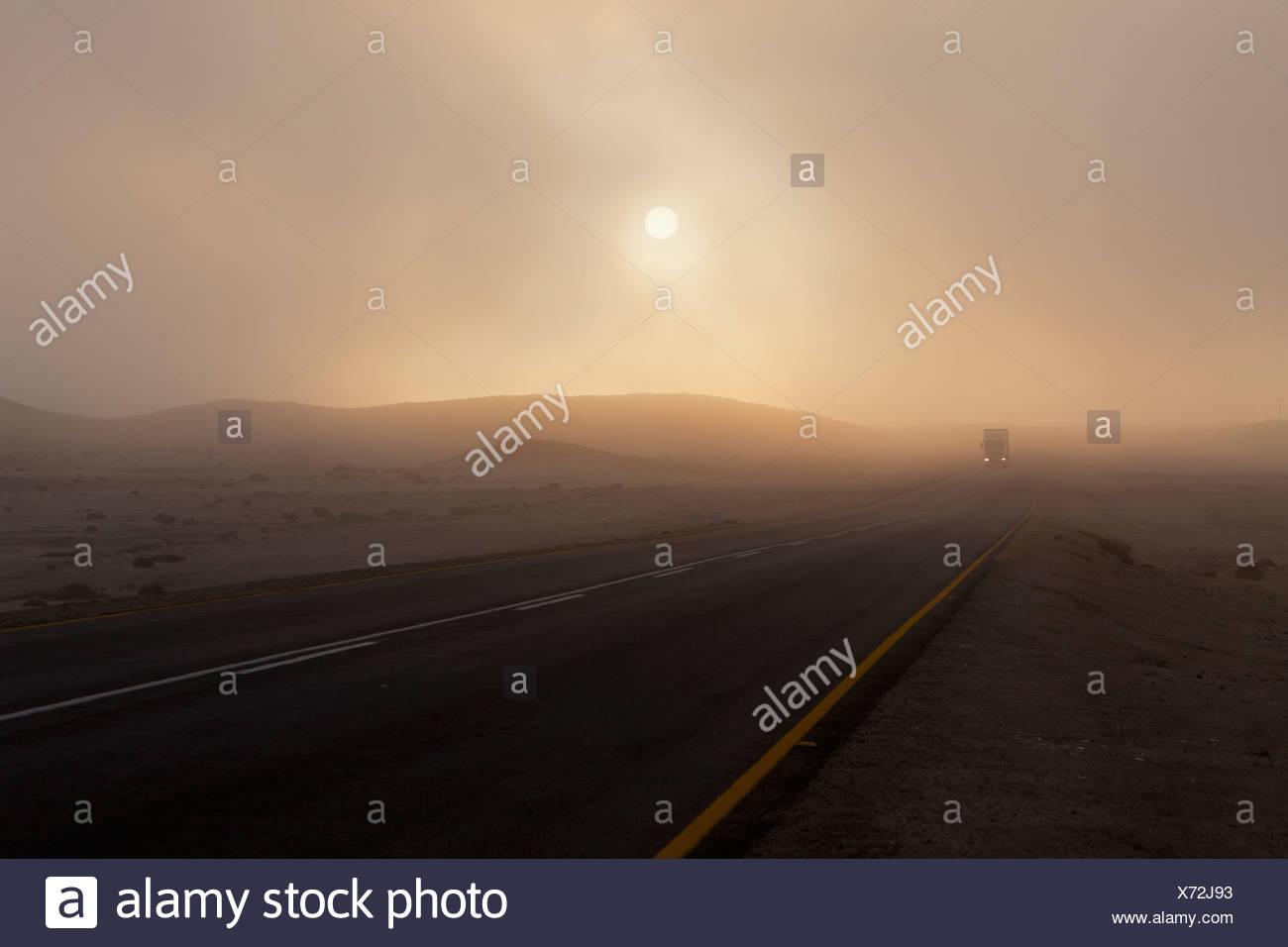 Afrika, Namibia, Namib Wüste, Swakopmund, Ansicht des Fahrzeugs auf nebligen Straße im Morgengrauen Stockbild