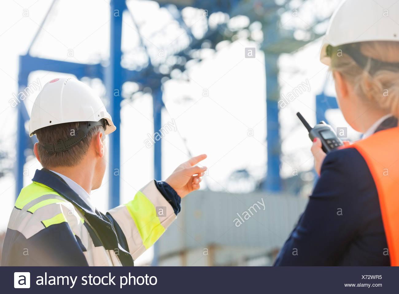 Männliche und weibliche Arbeitnehmer, die im Frachthafen Stockbild