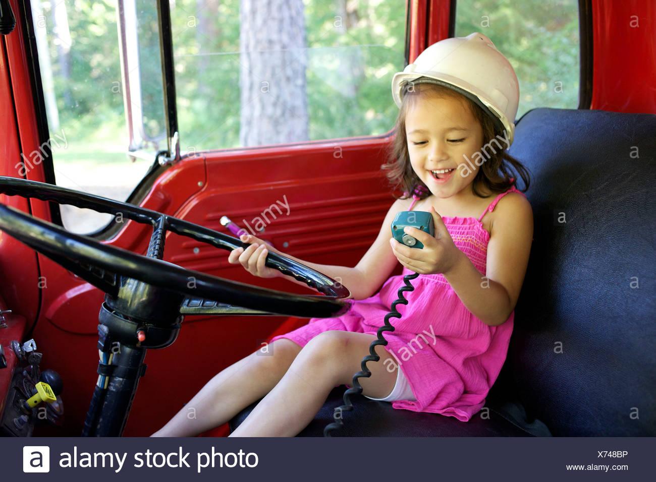 Ein junges Mädchen spielt mit einem Autoradio. Stockbild