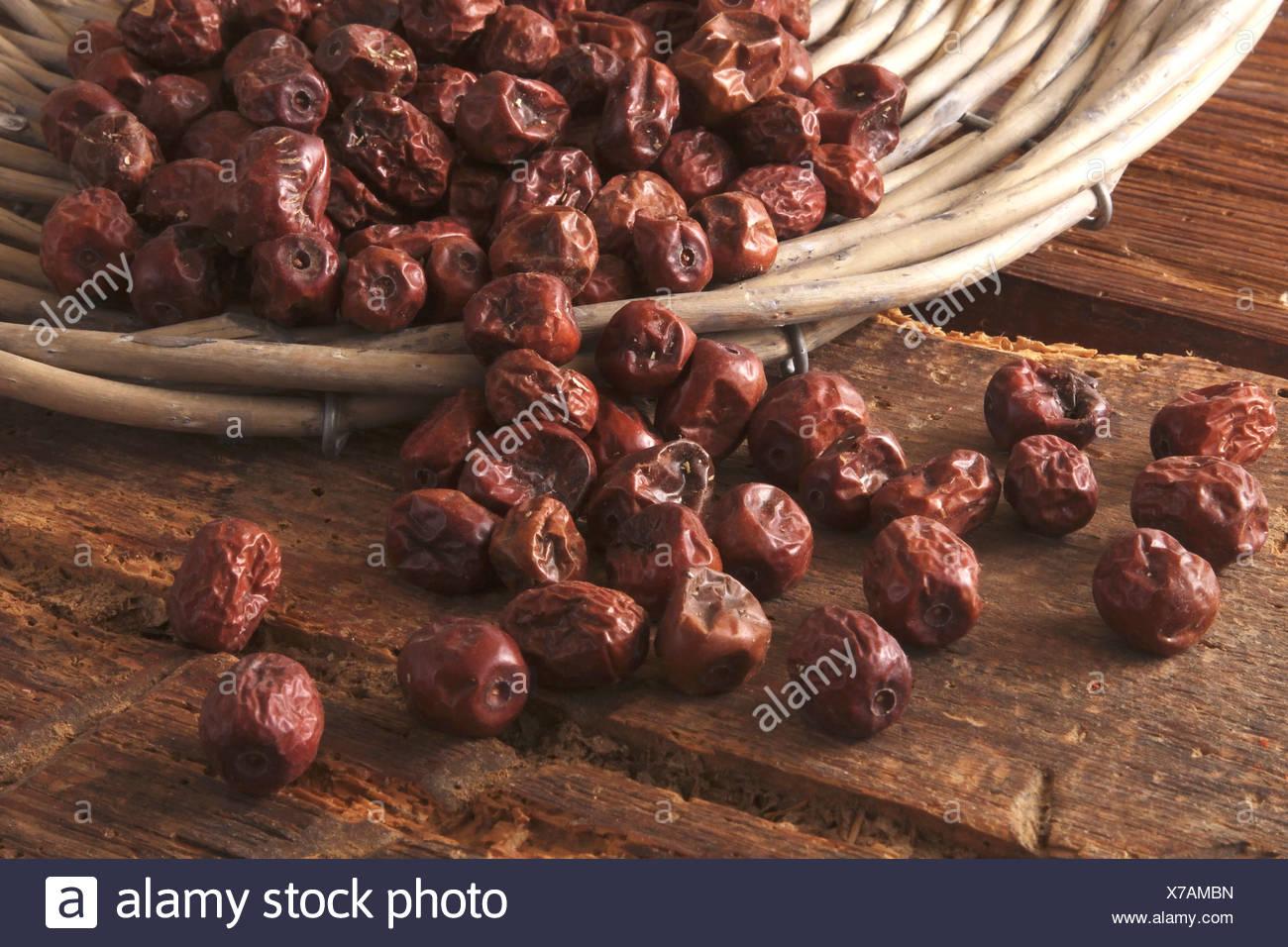 Getrocknete Beeren der Jujube (Ziziphus Jujuba) als Zutat für Müsli, Kuchen und Gebäck, aus einer Weide Korb gekippt Stockbild